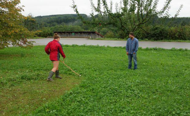 Devyn lernt Sensenmähen im taufrischen Gras. sie mäht mit einer sense des sensenvereins deutschland. Sebastian Brandl zeigt ihr den richtigen Schwung beim Sensenmähem.