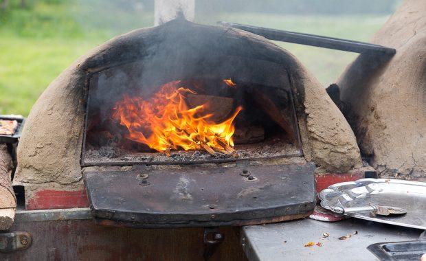Hier wird das Feuer im Lehmofen mit kleinen Spänen wieder entfacht. Am Ofen ist Ruß zu sehen. Es ist ein Blech und ein Pizzaschneider zu sehen.